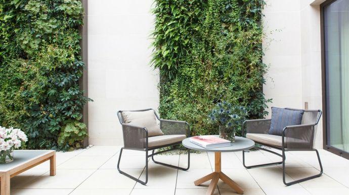Innenhof Einrichtung Gartenmöbel grüne Wand Holztisch Glastür