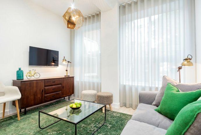 Modern graues Sofa grüne Deko Kissen Holzelemente-Wohnzimmer Einrichtung Ideen