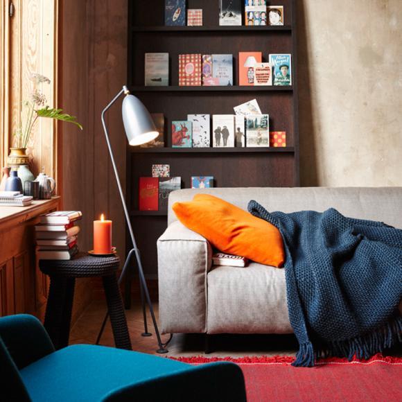 Wohnzimmer Deko Stehlampe modern offen Bücherregal Sofa Grau Kissen kuschelig Decke Arbeitstisch Bücher Orange Rot Blau-Wohnideen