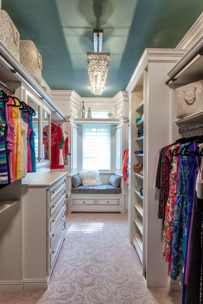 Blaue Wände, luxuriöser Kronleuchter und Sitzbank-Die Farbkombination wirkt erfrischend und behaglich.-Offener begehbarer Kleiderschrank in Weiß und Blau
