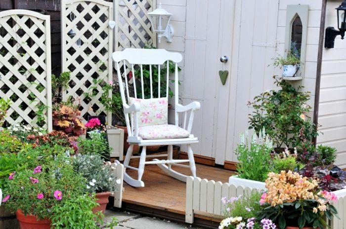Farbenfrohe Gartendeko mit Schaukelstuhl in Weiß-Rückzugsort Gartengestaltung mit Topfpflanzen Schaukelstuhl aus Holz