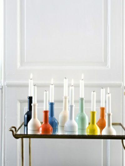 Farbenfrohe Kerzenhalter auf einem Glastisch-kleine Kerzenhalter