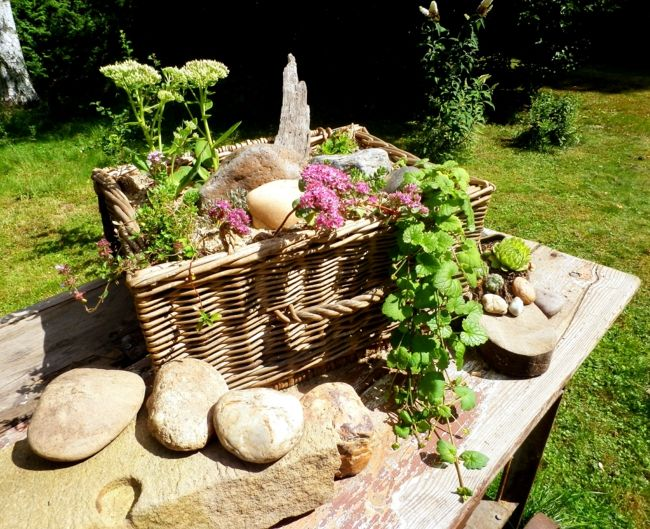 Gartentisch aus Holz mit großem Blumenkorb und Steinen als Dekoration Gartendeko - Ideen