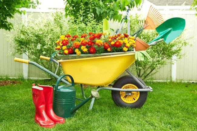 Gartenwerkzeuge, rote Gummistiefel, Gießkanne und Schubkarre mit bunten Blumen als einer abwechslungsreichen Ergänzung des ExterieursGartendeko - Ideen