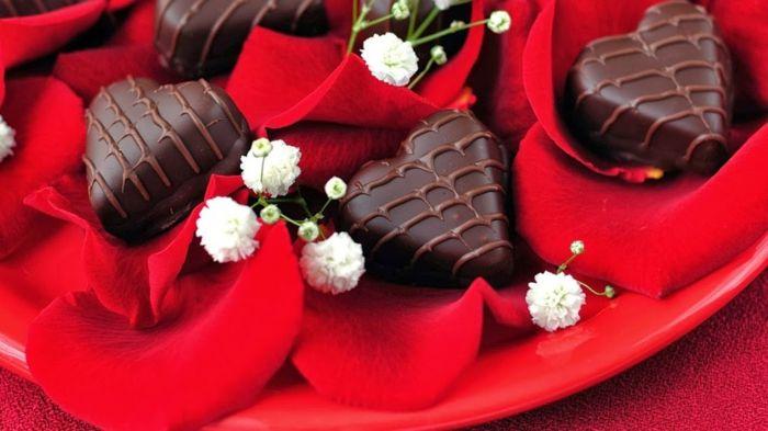 Pralinen in Herzform auf Rosenblättern-Romantische Stimmung mit passender Dekoration schaffen-Süßigkeiten Pralinen Schokolade Herzform Valentinstag Tisch Deko
