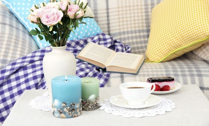 Rückzugsort mit Buch, Kerzen, Blumen und Leckereien gestalten-Wer lässt sich nicht gern auf dem Sofa verwöhnen-Dekoration Einrichtung Wohnzimmer Sofa karierte Textilien Stabkerzen Schnittblumen in Vase