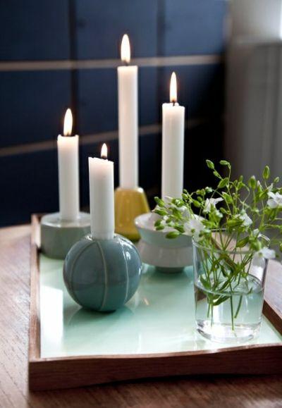 Weiße Stabkerzen und runden Kerzenhalter-Kerzenständer im Interieur