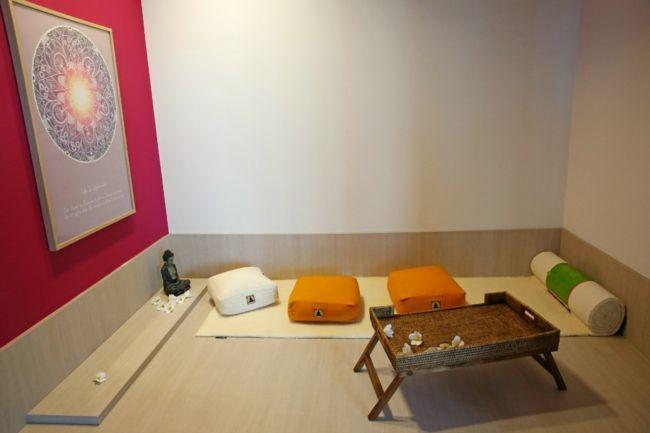 Yogaraum, Meditationskissen, Bodenkissen, Buddahfigur, Beistelltisch, rote Wand, Wanddekoration