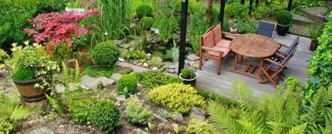 kleiner hübscher Garten mit rundem Gartentisch aus Holz Gartendeko - Ideen