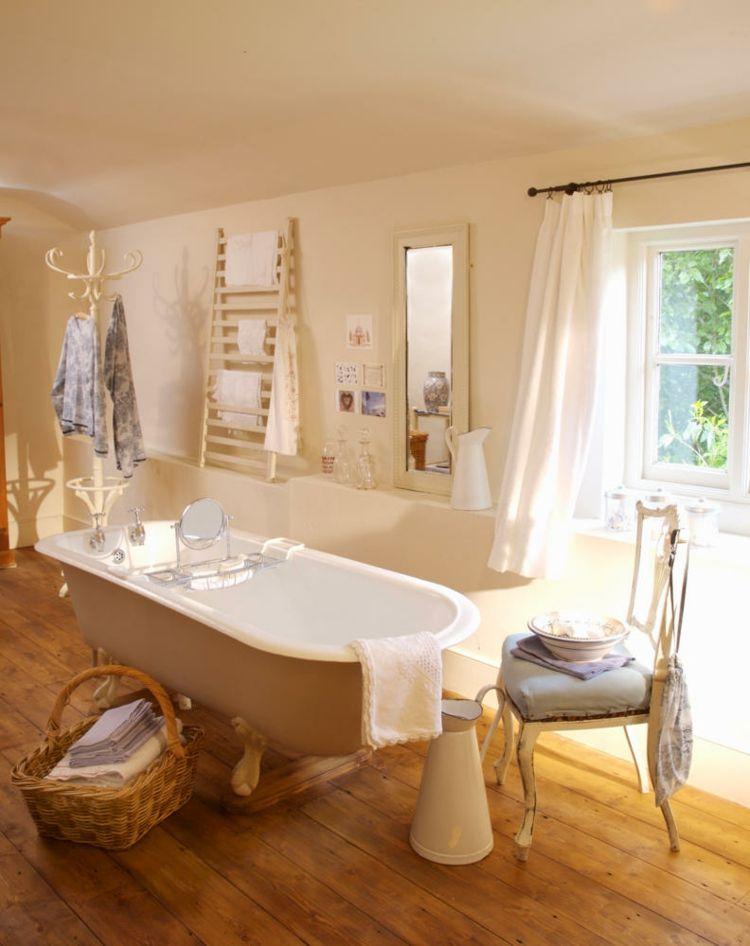 Freistehende Badewanne im Vintagestil vor Fenster im Badezimmer eines Landhauses