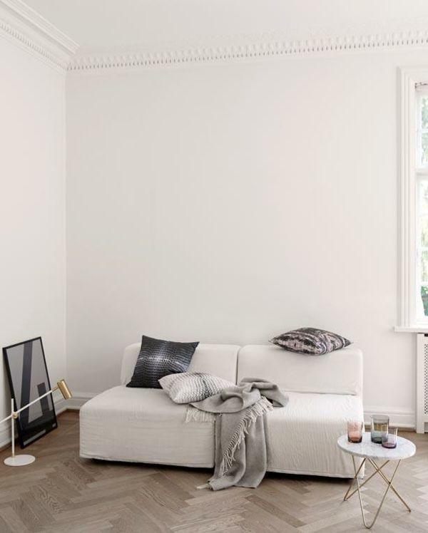 Wohnzimmer weiß Sofa minimal Laminatboden Fischgrätmuster