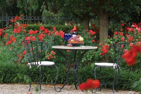 rote Gartenmöbeln umgeben von bezaubernd duftenden Rosen
