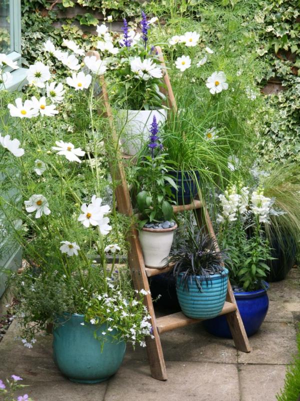 Holzleiter als Blumenregal für bunte Keramiktöpfe in den Garten