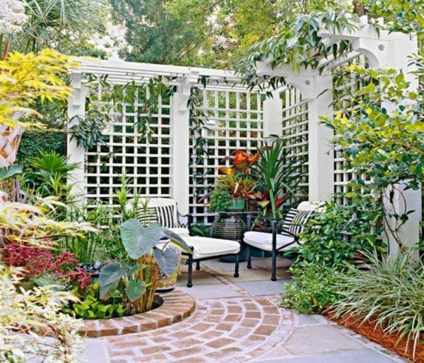 weißes Spalier grenzt einen gemütlichen Bereich im Garten