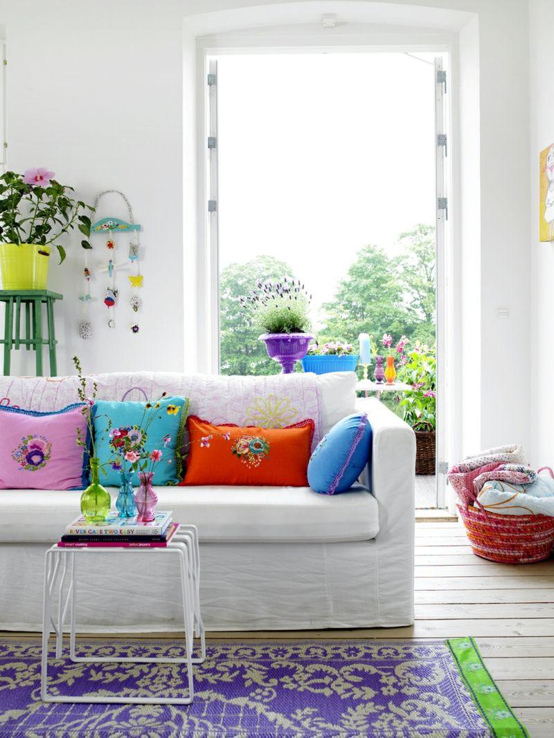 Bunte Dekokissen und Teppiche verbreiten im Wohnzimmer gute Frühlingslaune