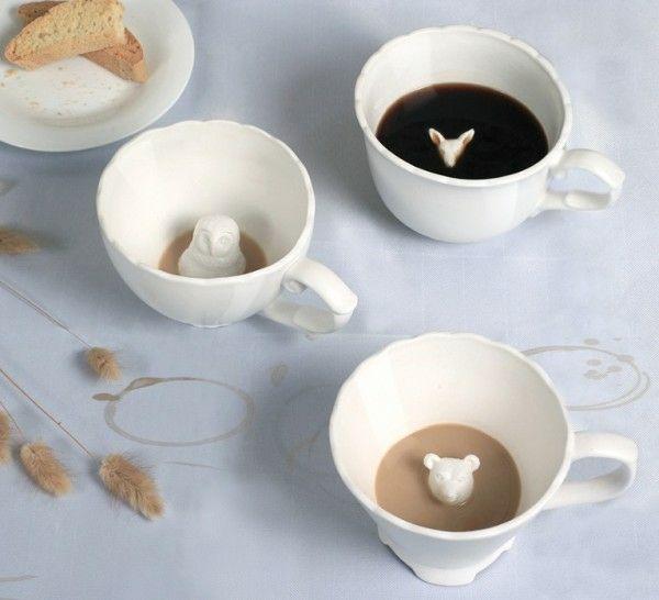 Extravagante Kaffeetassen mit Tierabbildungen am Boden.