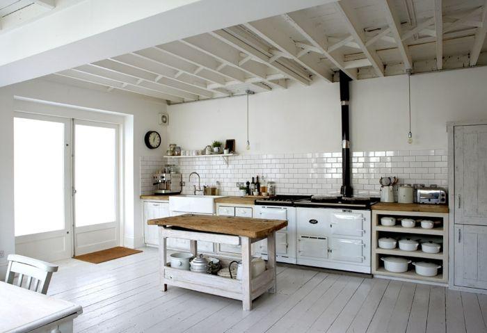 Eine rustikale Küche mit weißen Küchenmöbeln und Dielenboden