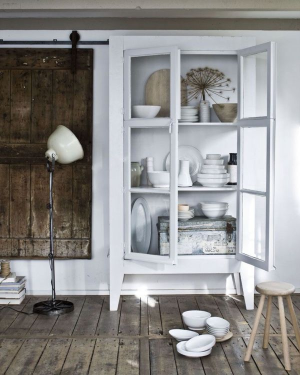 In einem Küchenschrank mit Vitrinentüren wird feinstes Porzellan gut sichtbar gemacht