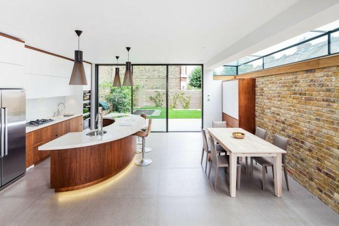 Küche Einrichtung kurvig Steinwand Insel weiß Esstisch