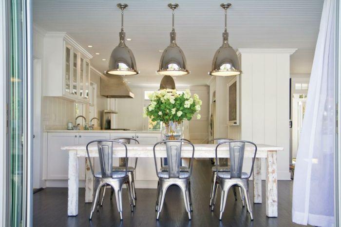 Weiße Blumen auf dem weißen Tisch ergänzen das Gesamtbild dieser stilvollen Küche