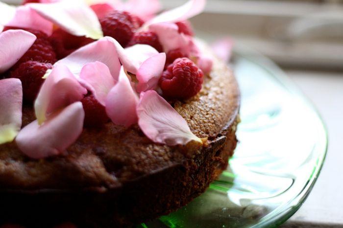 Kuchen mit Rosen und Himmbeeren schmückt den Tisch