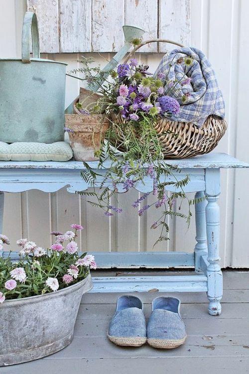 blauer Tisch Wiesenblumen Metallgefäß Geflechtkorb