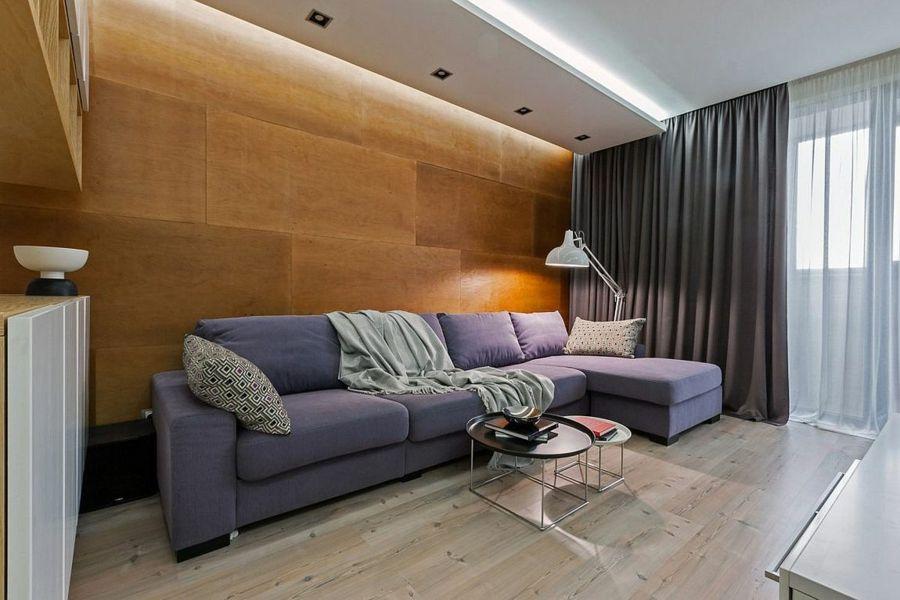 Die grauen Textilien lassen sich ideal mit der Holzwand kombinieren