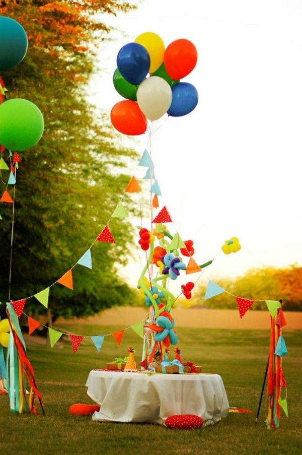 Outdoor Kinderparty Luftballons bunte Fahnenkette rote Bodenkissen