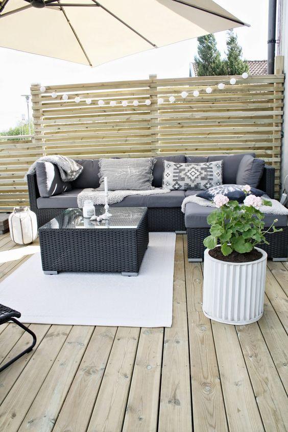 Rattanmöbel Sonnenschirm Holzboden graue Deko Kissen Outdoor Holzwände