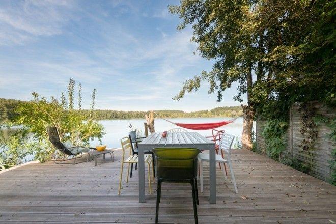 modern-terrasse-und-balkon-am-see-holztisch-hangematte