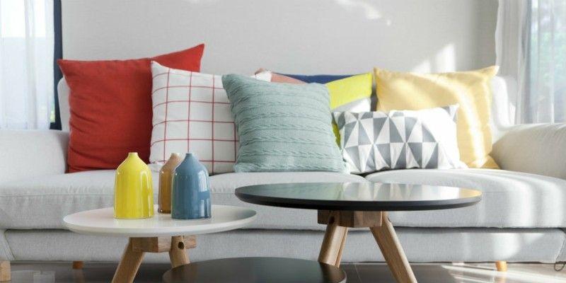 bunte-deko-kissen-auf-der-couch-und-eine-kleine-vase-im-vordergrund