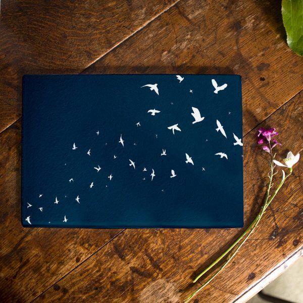 eine-vogelschar-auf-dunkelblauem-schneidebrett