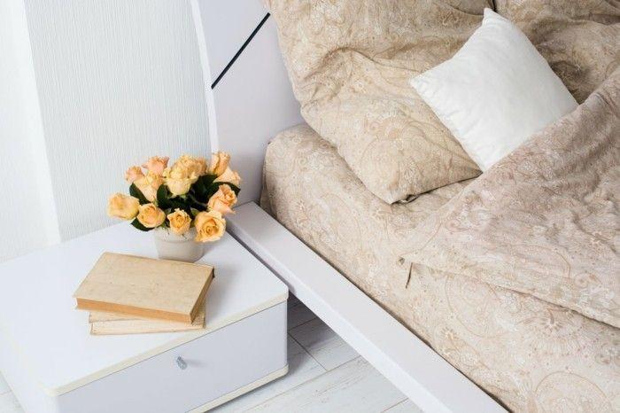 stilvoll-und-gemutlich-eingerichtet-beige-bettzeug-blumen-auf-dem-nachttisch