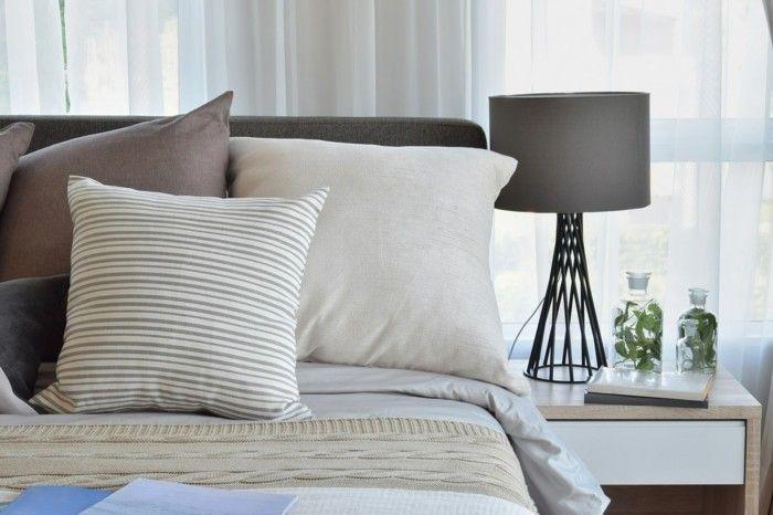 stilvolles-schlafzimmerinterieur-in-braun-braun-gemusterte-kissen-auf-dem-bett-und-dekorative-nachttischlampe