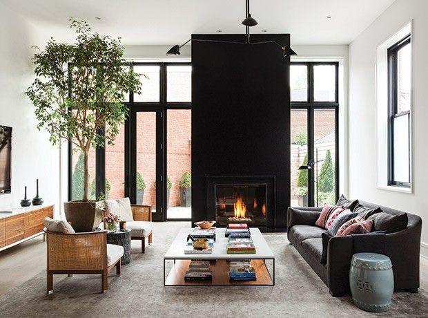 schwarze-kaminwand-schwarze-fensterrahmen-schwarze-couch-helle-wandfarbe-heller-teppich-holzmobel-grun-im-zimmer