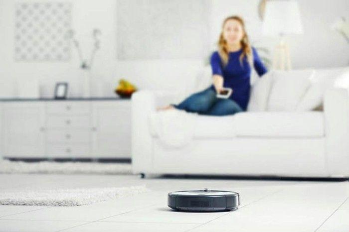 roboter-staubsauger-reinigt-das-zimmer-wahrend-frau-auf-der-couch-sitzt