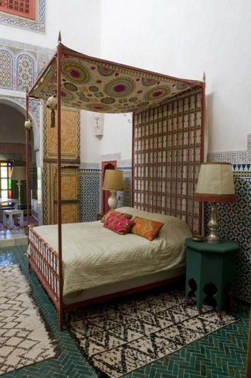 Marokkanisches Schlafzimmer handgewebte Stoffe über und am Schlafbett Teppiche Mosaik an der Wand bunte Deko Kissen