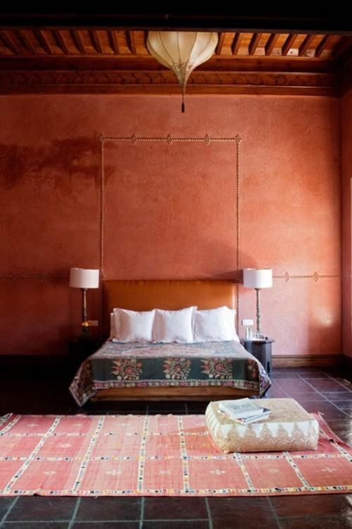Marokkanisches Schlafzimmer in warmen Farben schön gemusterter Teppich ein quadratischer Sitzhocker darauf
