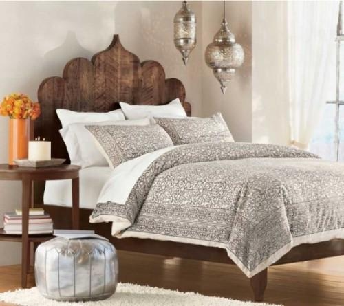 Marokkanisches Schlafzimmer neutrales Design dunkles Holz helles Bettdecke silberfarbener Hocker Hängeleuchten