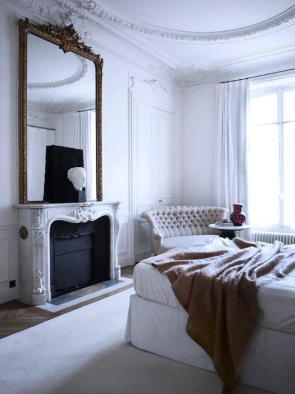 Pariser Chic im Schlafzimmer Kamin hoher Wandspiegel bequemes Polstersofa großes Schlafbett Deko Artikel