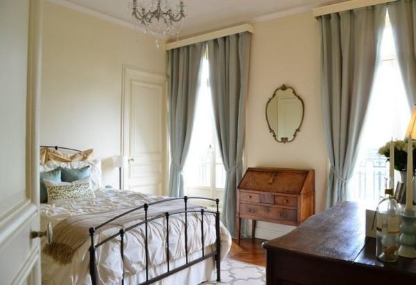 Pariser Chic im Schlafzimmer Metallbett Retro Touches Spiegel alte Kommode graue Gardinen Kristall-Kronleuchter