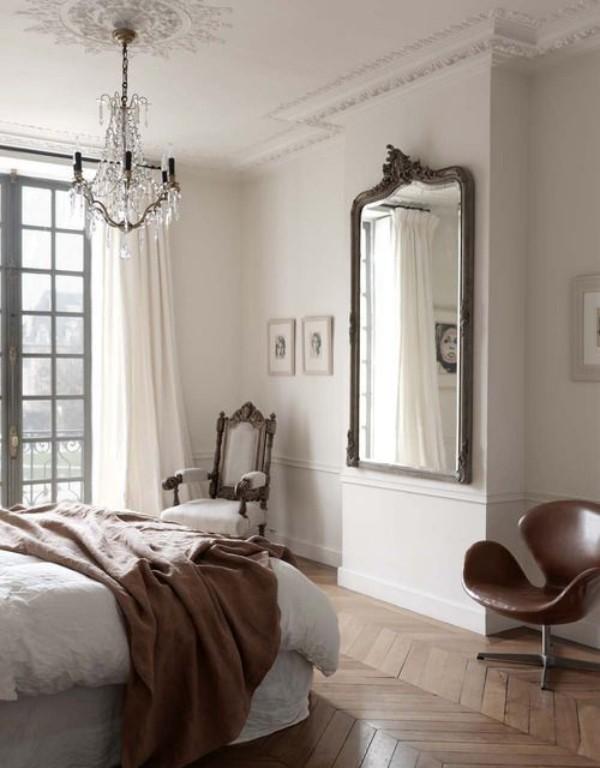 Pariser Chic im Schlafzimmer Parkettboden Spiegel gegenüber dem Schlafbett klassischer Sessel in der Ecke noch ein moderner links im Vordergrund Kristall-Kronleuchter Wurfdecke