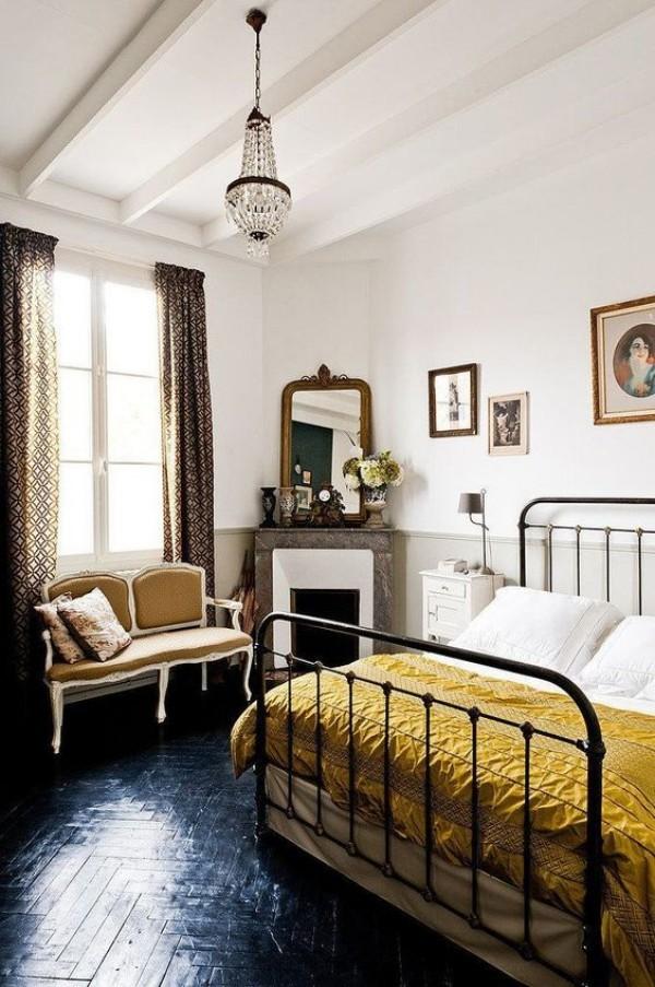 Pariser Chic im Schlafzimmer dunkler Parkettboden goldgelbe Tagesdecke Retro Elemente Metallbett Kamin Spiegel Bilder