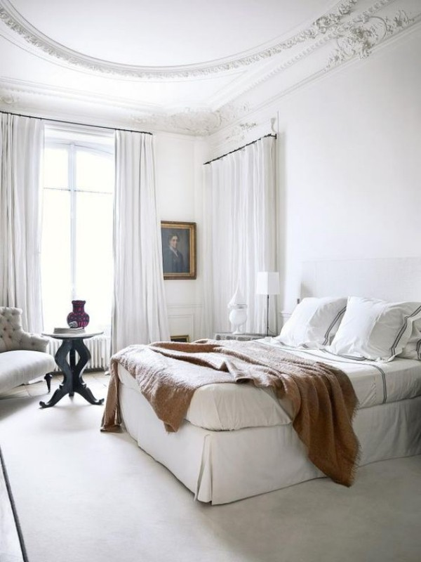 Pariser Chic im Schlafzimmer helles Ambiente Charme und Stil Wandgemälde Wurfdecke auf dem Schlafbett Sessel kleiner Tisch