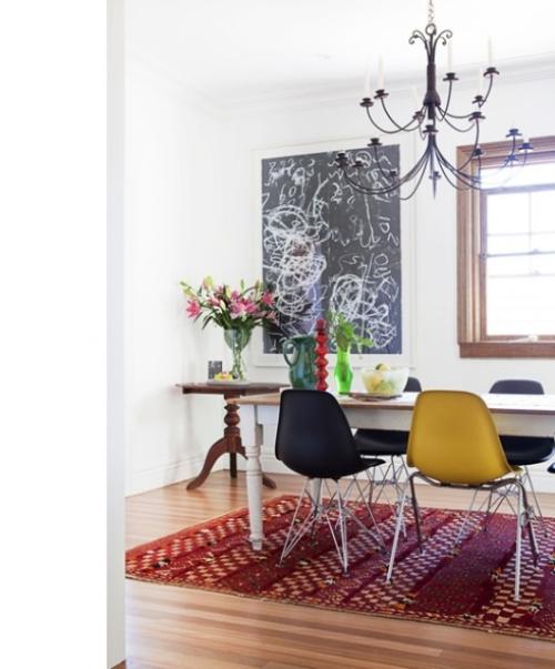 Boho Chic im Esszimmer Holztisch Plastik Stühle bunter Teppich als Akzent Blumen