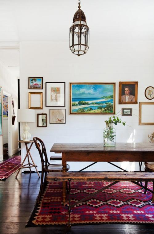 Boho Chic im Esszimmer Wandbilder schön gemusterter Teppich massiver Esstisch aus Holz