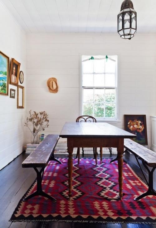 Boho Chic im Esszimmer langer Holztisch zwei Sitzbänke gemusterter Teppich Wandbilder
