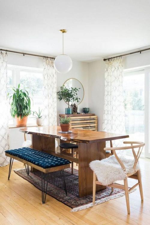 Boho Chic im Esszimmer viel Holz grüne Pflanze Kunstpelz auf dem Stuhl Holztisch gepolsterte Sitzbank