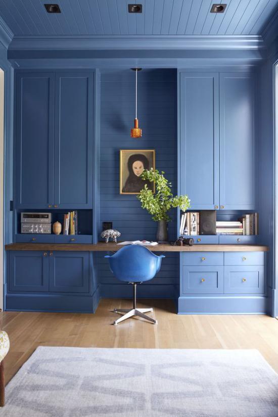 Farben fürs Heimbüro sehr stilvolle Einrichtung und Raumgestaltung in sanftem Blauton Bücherschrank in Blau Wandbild blauer Stuhl hellgrauer Teppich