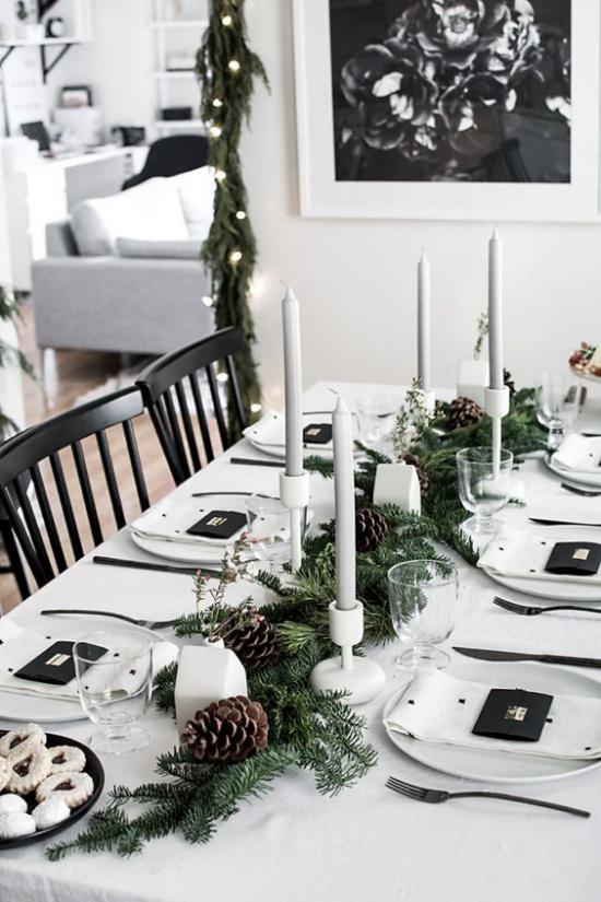 Festliche Tischdeko Ideen zu Weihnachten sehr stilvoll in Kontrast weiß-schwarz Tannengrün in der Mitte Zapfen